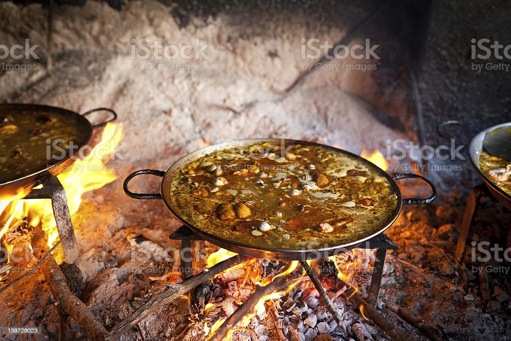 Pot of paella Valencia cooking on log fire near other pots royalty-free stock photo