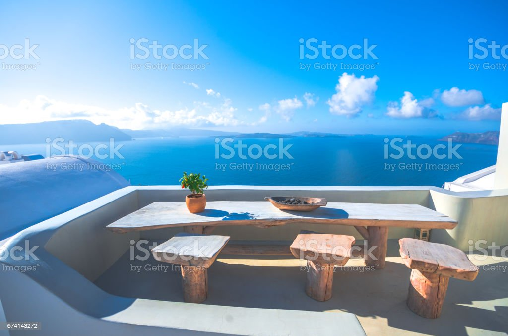 A pot with flower and a plate on a wooden table with ocean background, Santorini, Greece stock photo