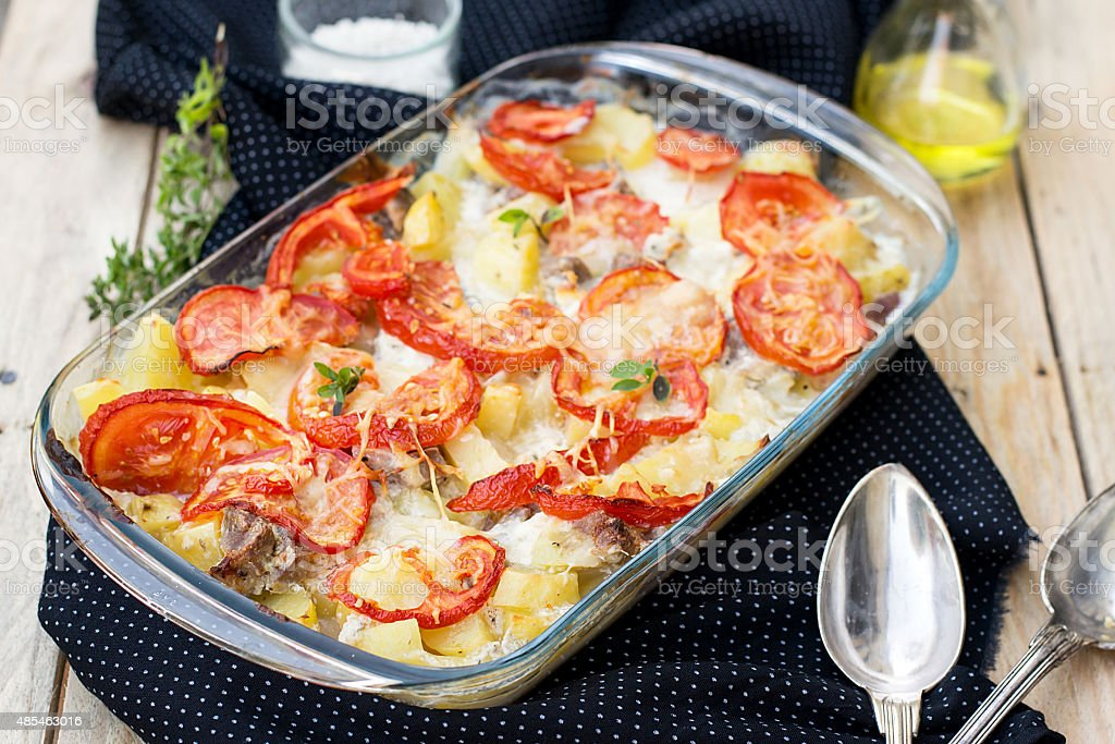 Potato and pork gratin with tomatoes stock photo