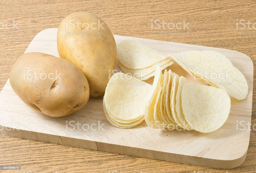 Potato and Potato Chips or Crisp on Cutting Board stock photo
