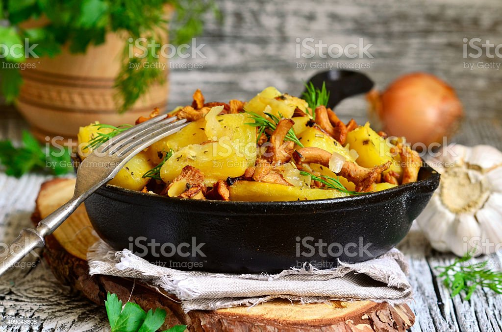 Potato baked with chanterelles,onion and dried herbs. stock photo