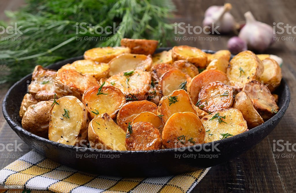Potato baked with dill in pan stock photo