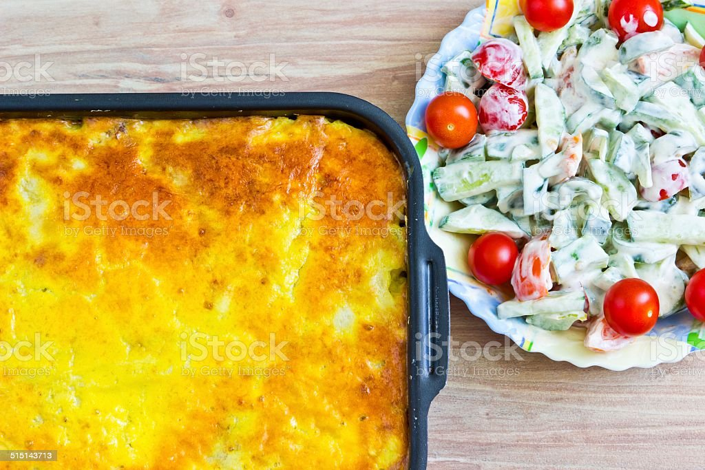 Potato casserole with eggs and meat. Fresh vegetable salad stock photo