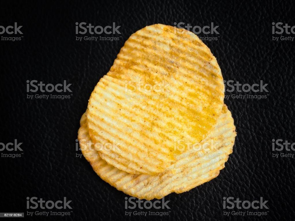 Potato chip on black background stock photo