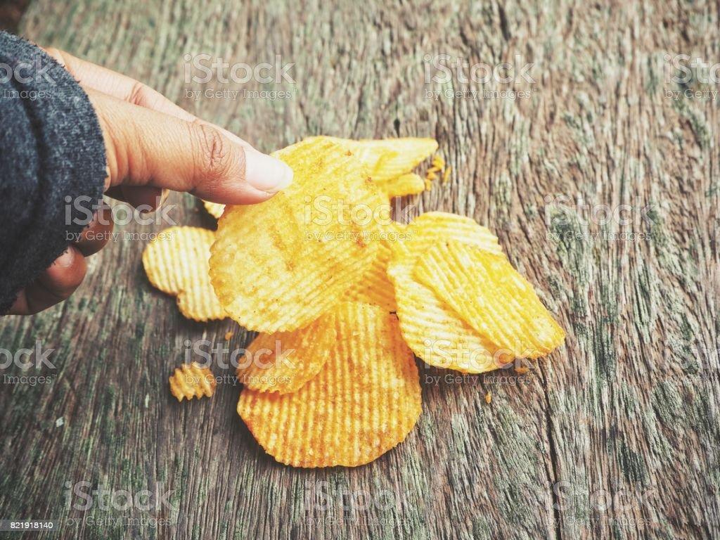 Potato chip with hand stock photo