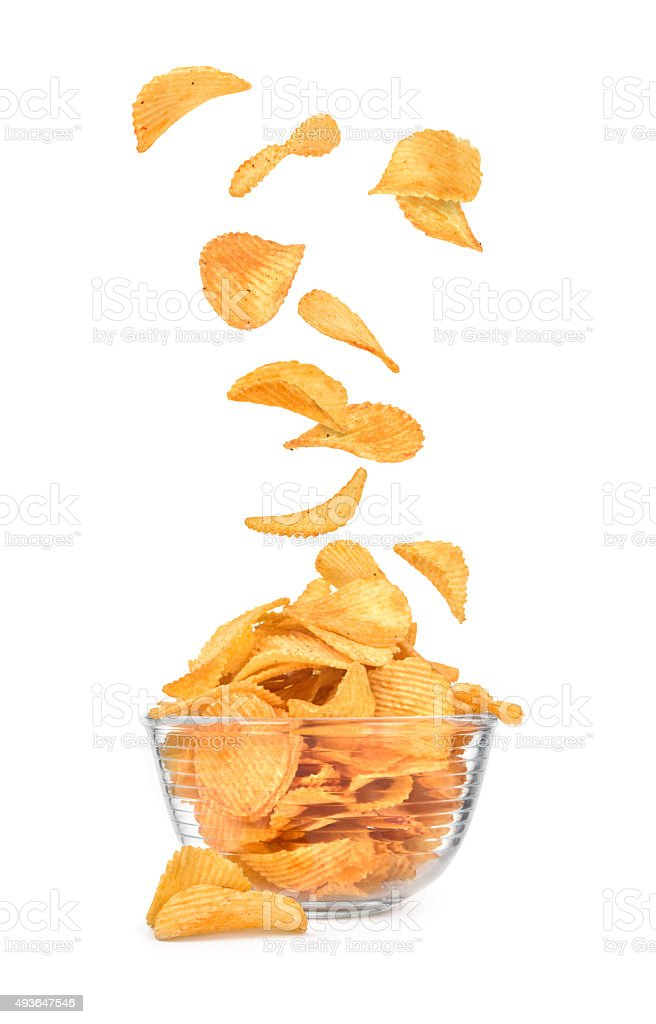 Potato chips falling in a bowl isolated on white stock photo