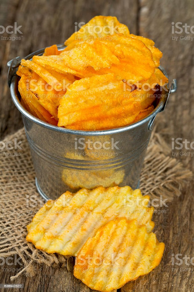 potato chips in a bucket on wooden surface stock photo