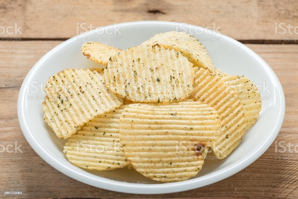 Potato chips in a white plate on wood background. stock photo