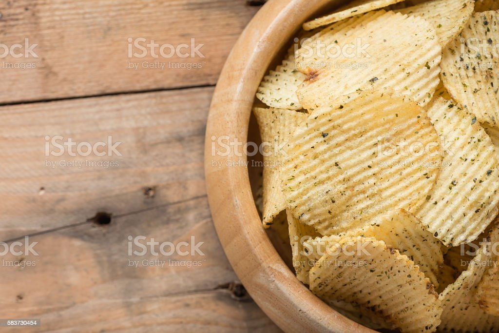 Potato chips in  wooden bowls on wood background. stock photo