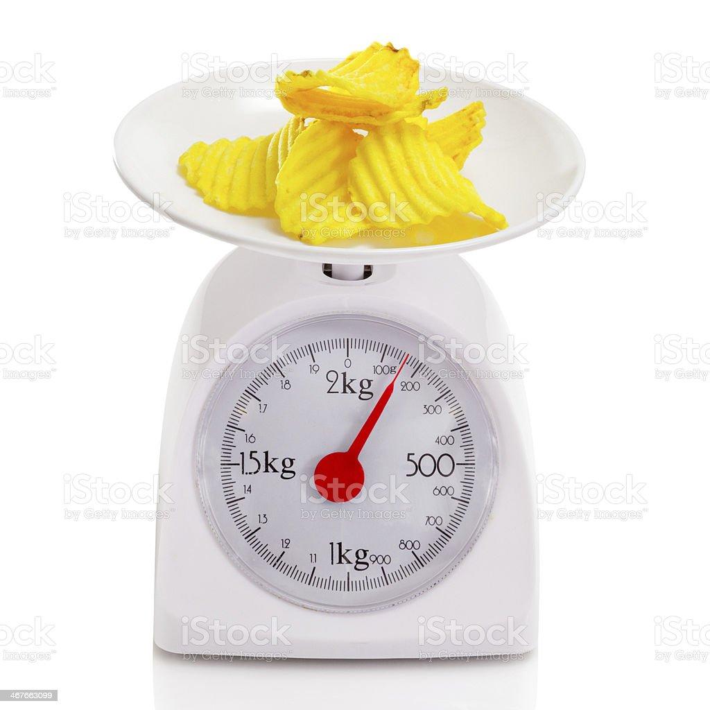 Potato chips on balance scale royalty-free stock photo