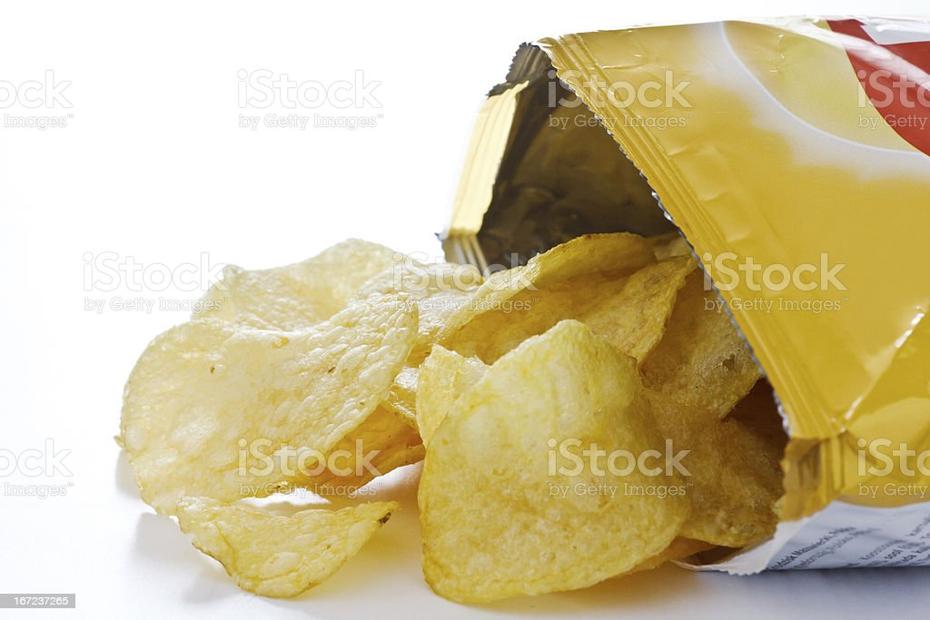 Potato crisp packet opened with crisps spilling out stock photo