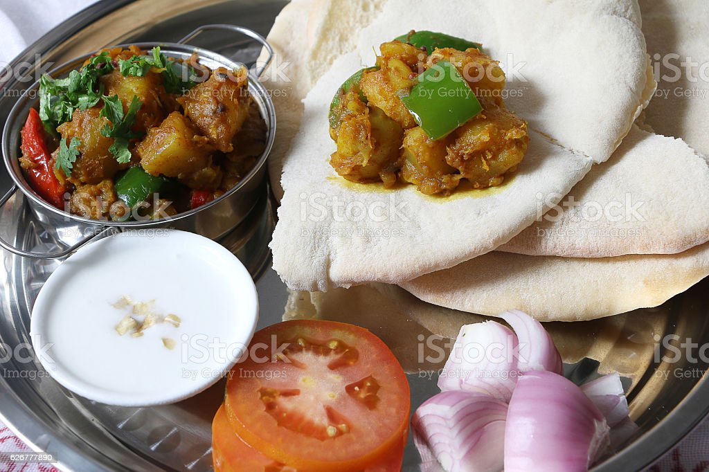 Potato curry aloo served with flat bread stock photo