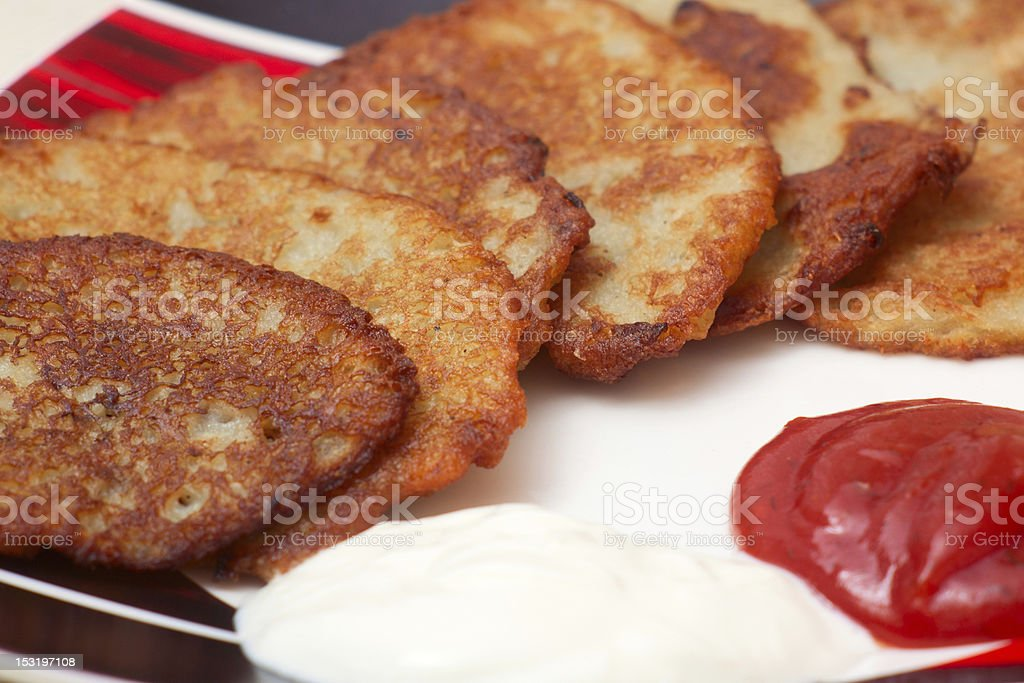 Potato pancake with sour cream and ketchup vector art illustration