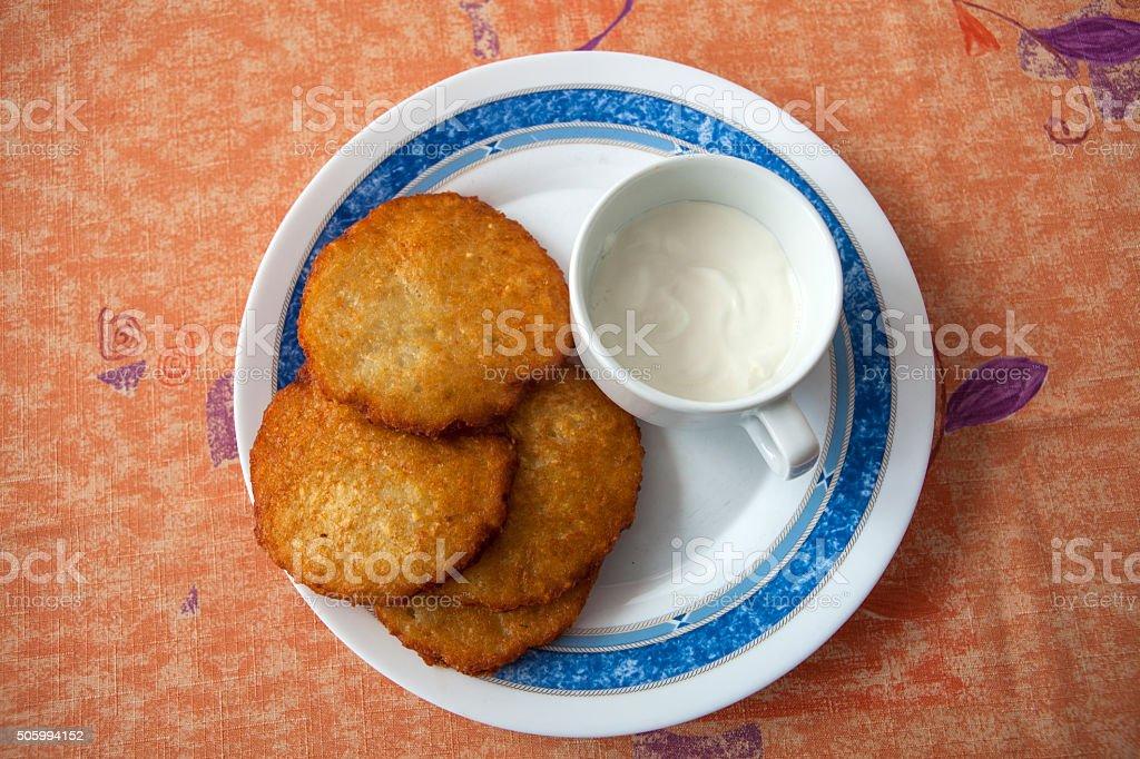 Potato pancake with sour cream stock photo