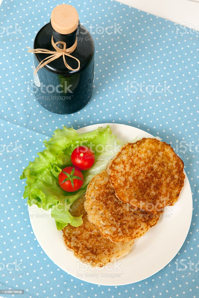 potato pancakes and a bottle of olive oil stock photo