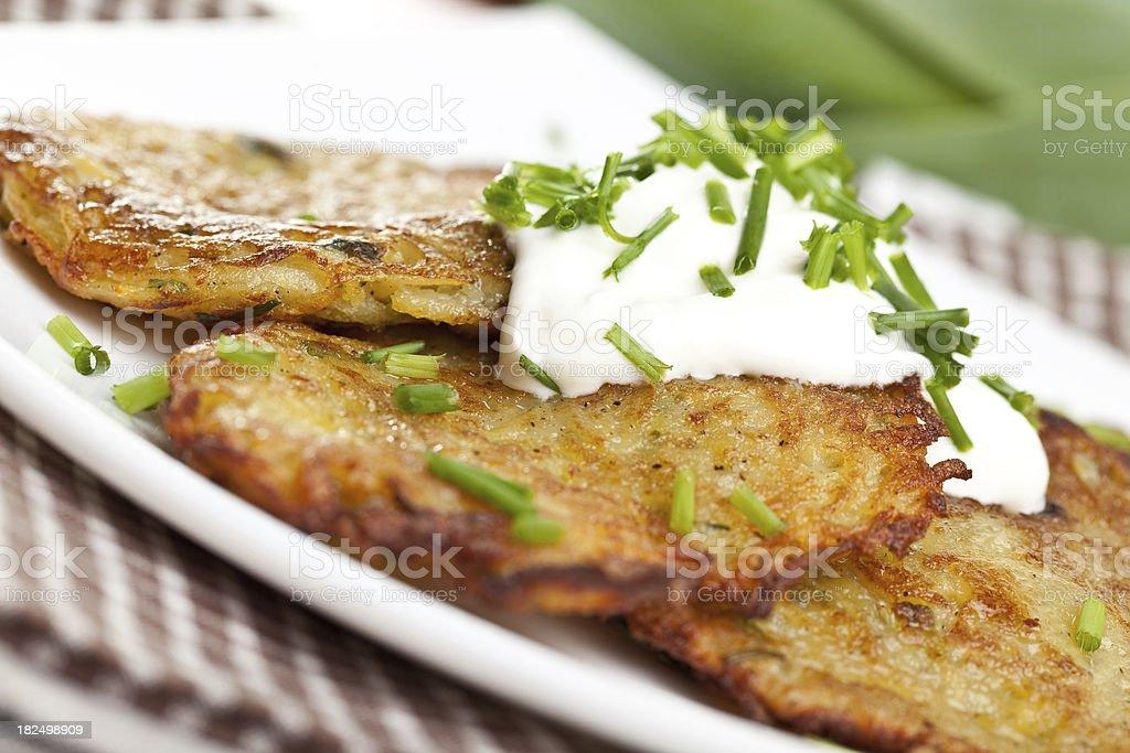 Potato pancakes on plate with sour cream stock photo