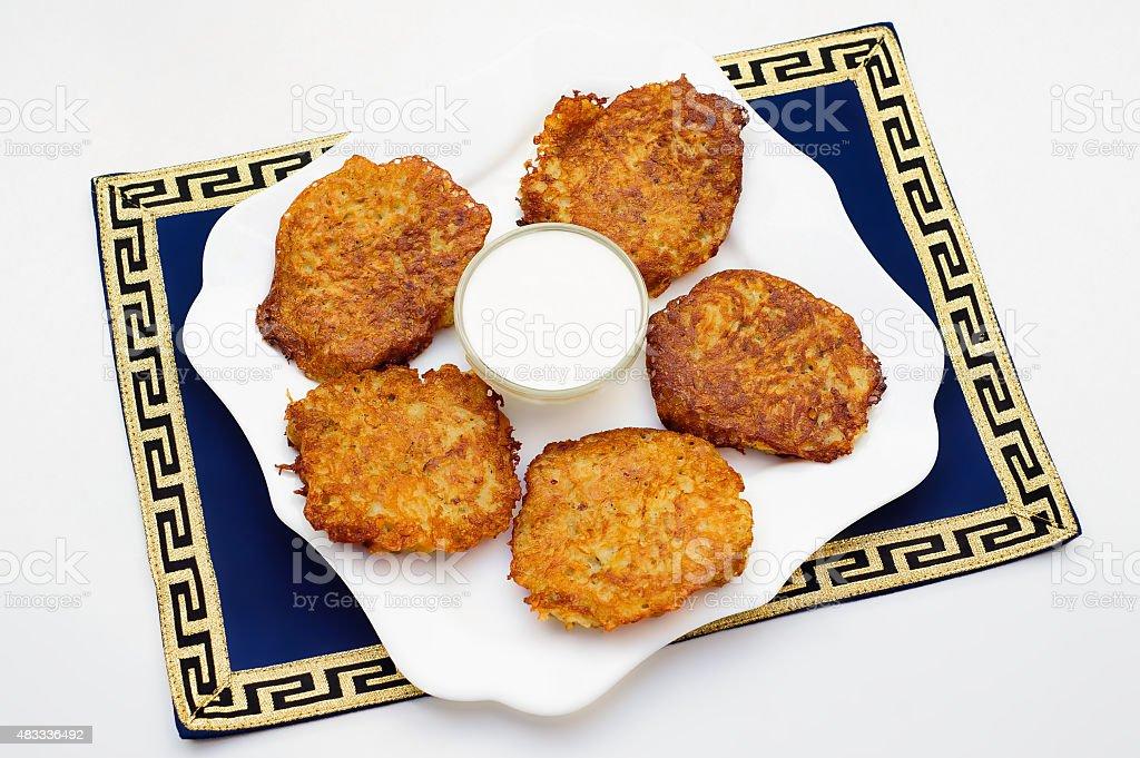 Potato pancakes with sour cream on the white plate stock photo