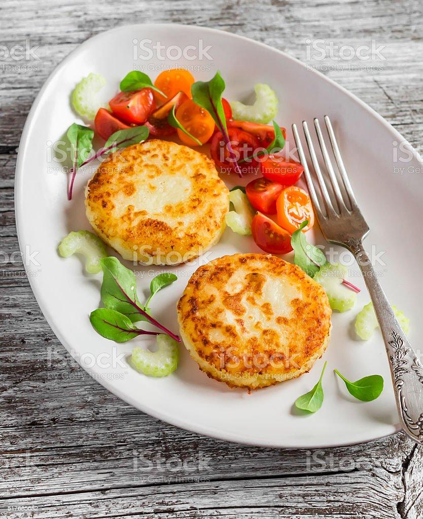 Potato patties and fresh tomato and celery salad stock photo
