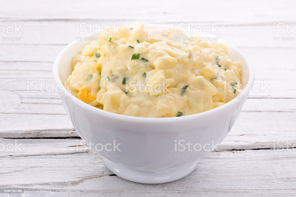 potato salad in white bowl stock photo