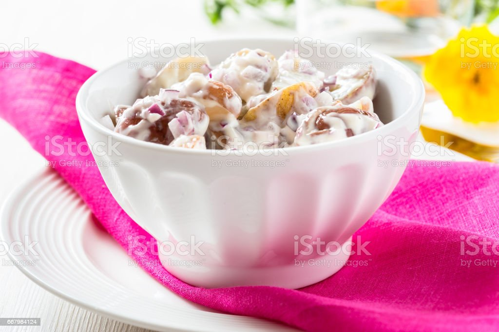 Potato salad made with  boiled baby potatoes, mayonnaise, mustard and chopped red onion stock photo