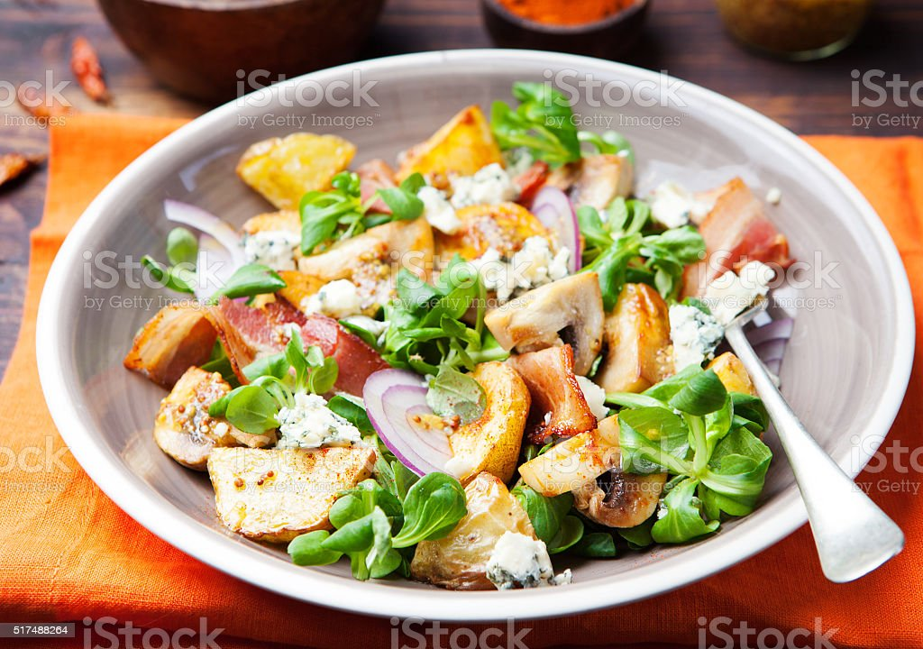 Potato salad with bacon, mushroom on orange napkin Wooden background stock photo