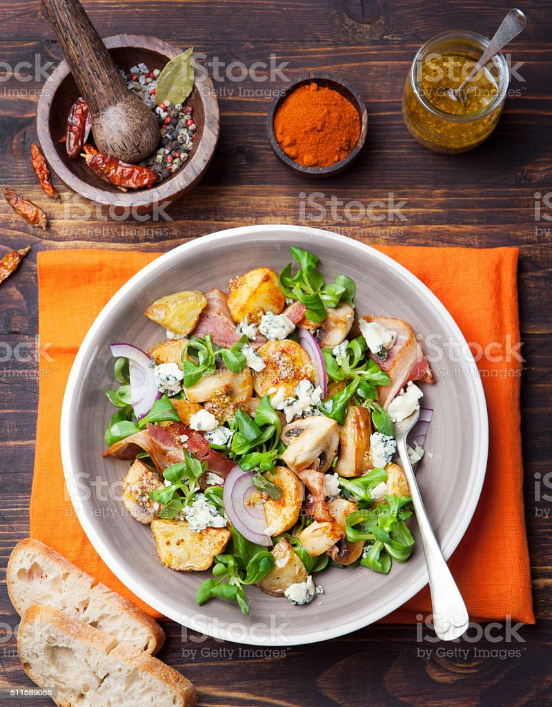 Potato salad with bacon, mushroom Wooden background Top view stock photo