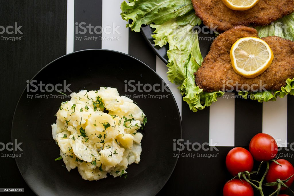 potato salad with schnitzel at restaurant. stock photo