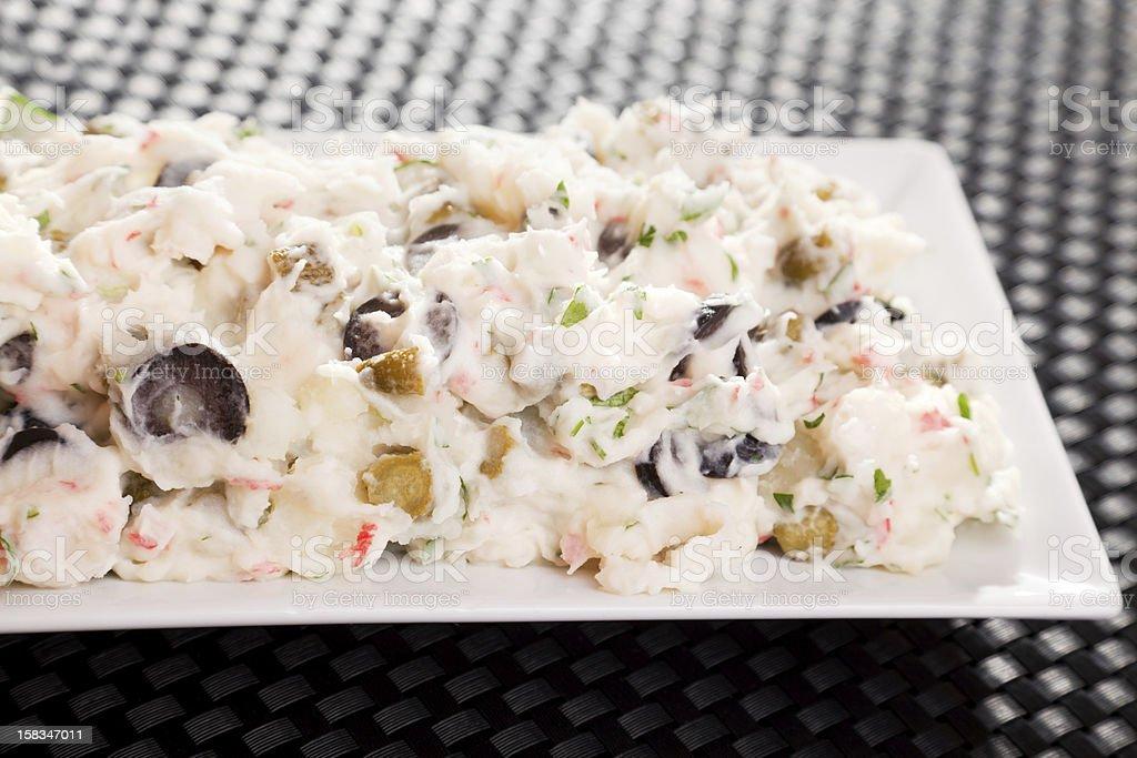 Potato salad with surimi and black olives stock photo