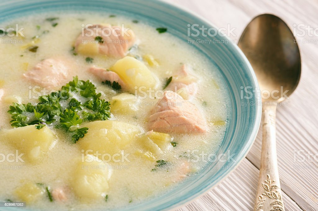 Potato soup with salmon, leek, sour cream and parsley. stock photo