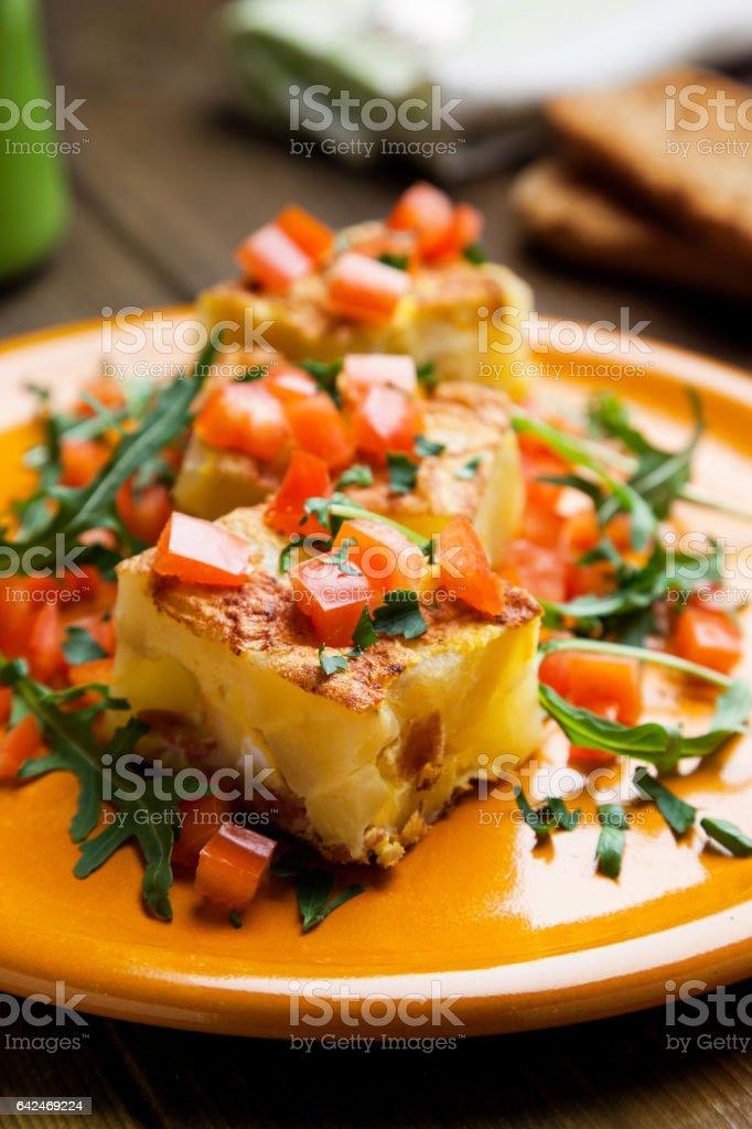Potato tortilla prepared with arugula and tomatoes pieces stock photo