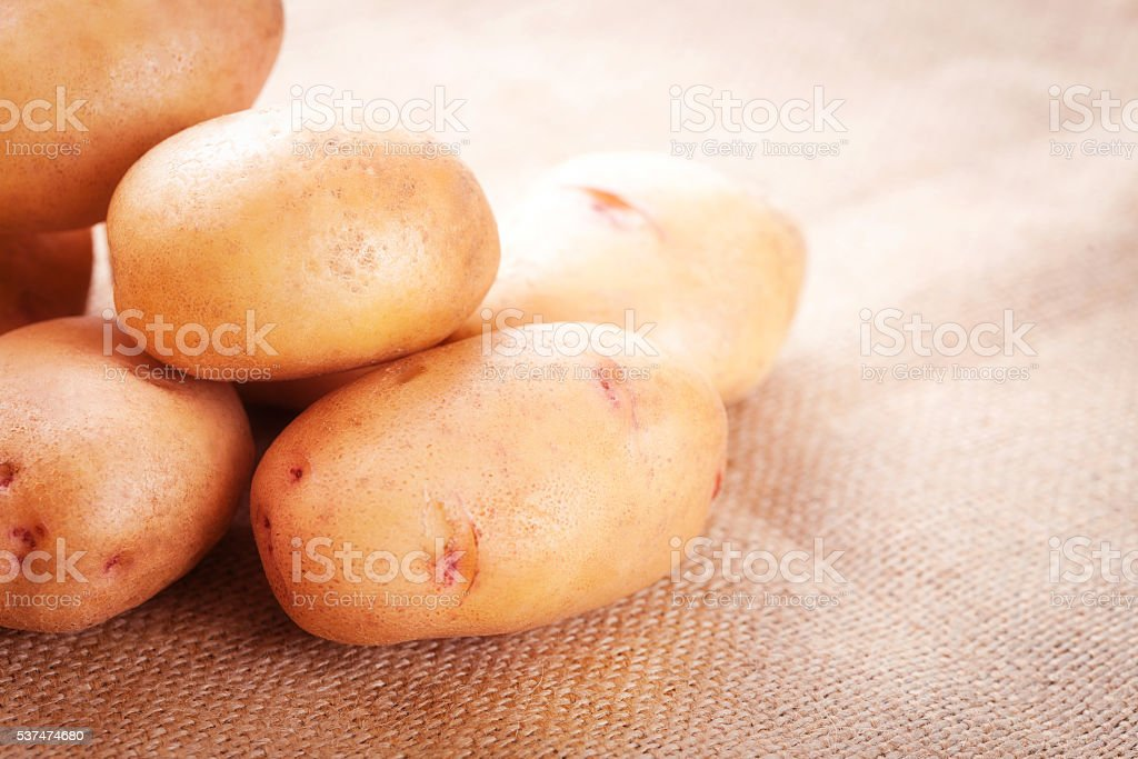 Potato tubers on a table close-up stock photo