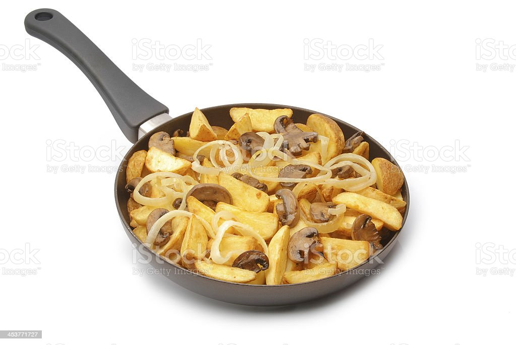 Potato wedges with mushrooms and onion fried on the pan. royalty-free stock photo