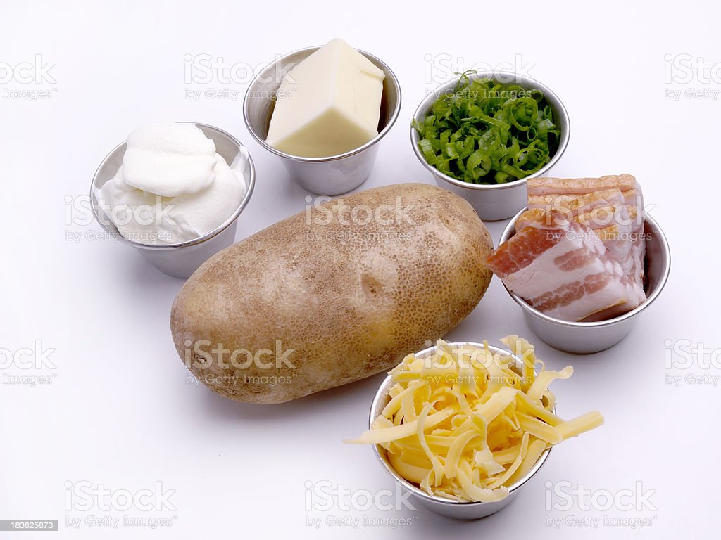 Potato with condiments for baking stock photo