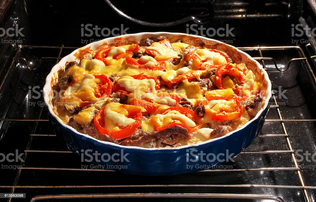 Potato with meat, tomato and cheese baked in the oven. stock photo