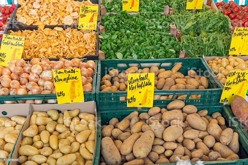 Potatoes and other vegetables at a market stock photo