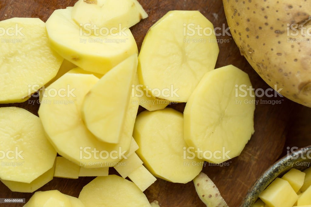 Potatoes and potato sliced on wooden table. Selective focus stock photo