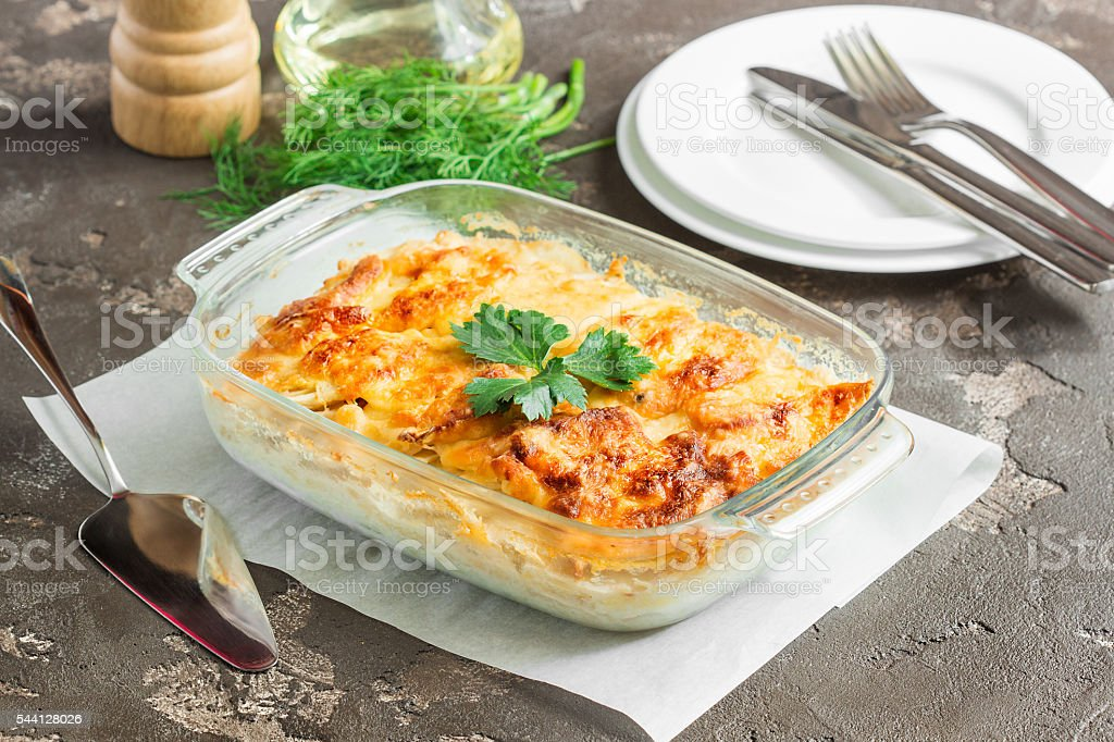 Potatoes baked with cheese, apples and vegetables stock photo