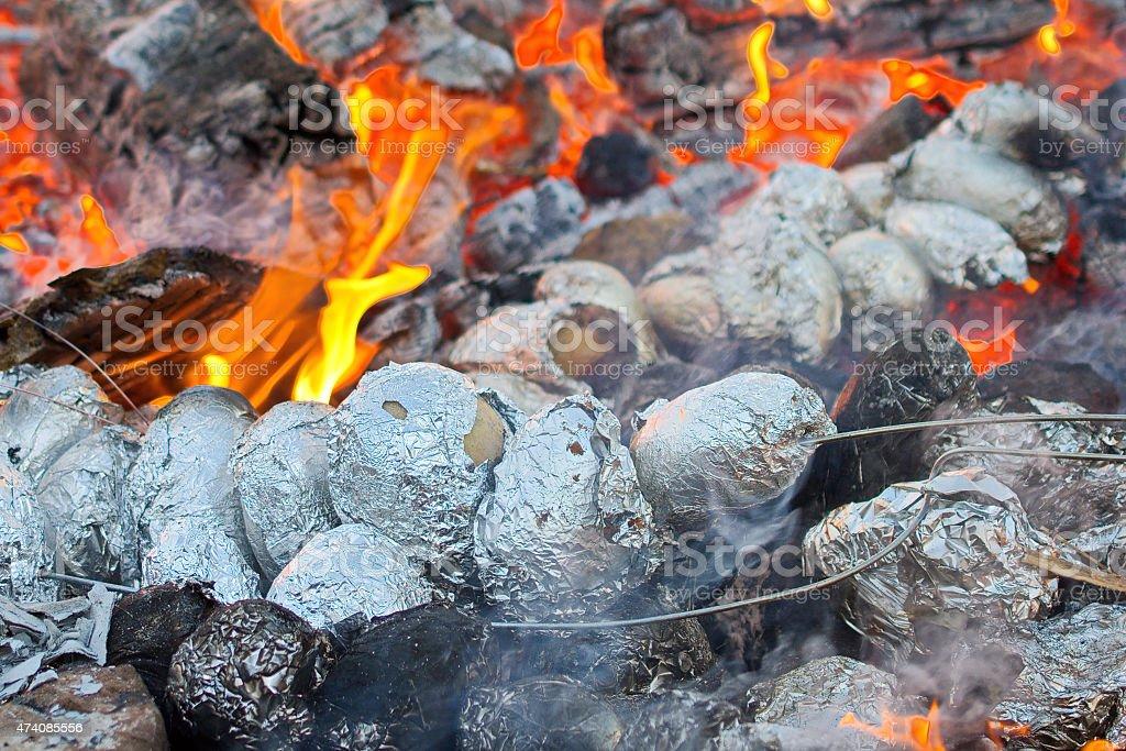 Potatoes baking in a bonfire stock photo