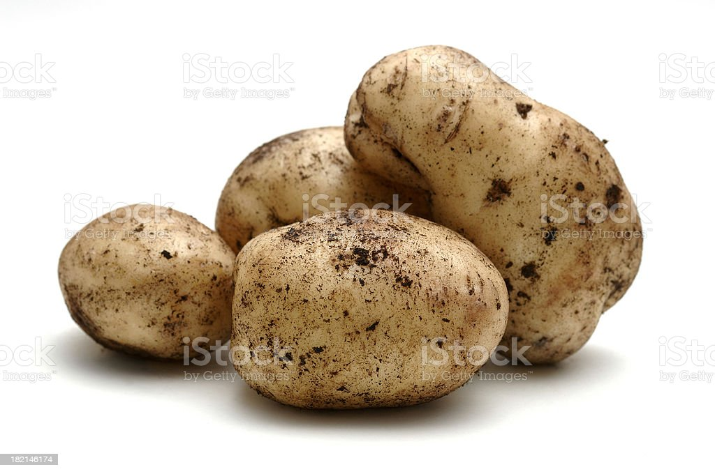 potatoes covered in soil against white stock photo