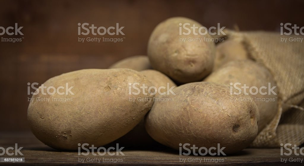 Potatoes from bag lying on wooden background stock photo