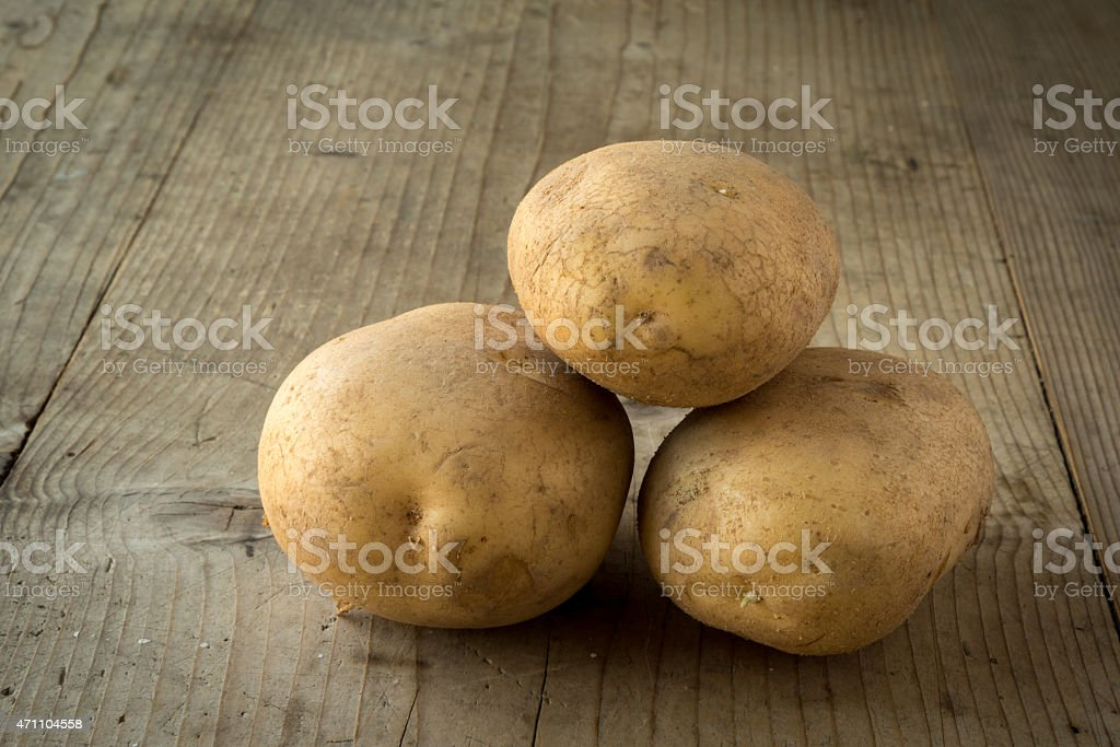 potatoes on wooden table stock photo