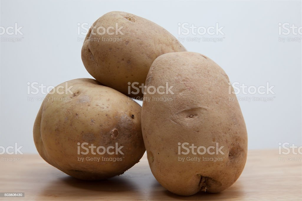 Potatoes stacked on clean wood board stock photo