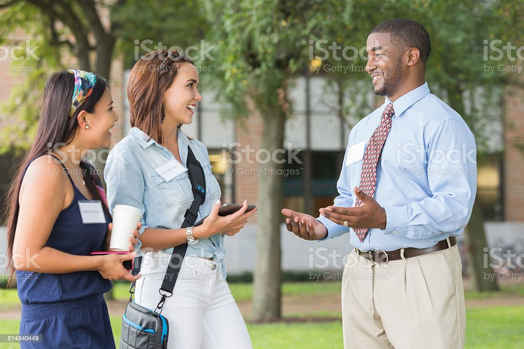 Potential college students touring campus with tour guide stock photo