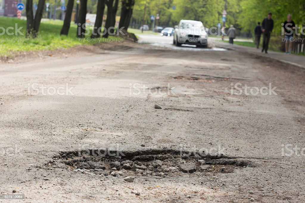 pothole on the road near the manhole stock photo