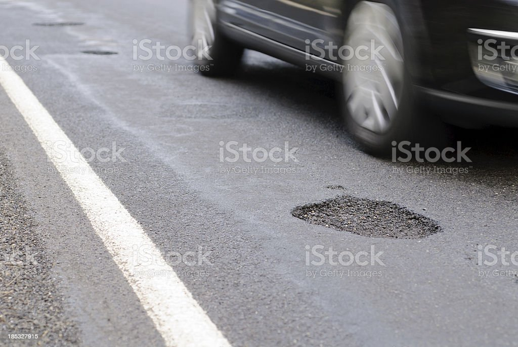 Pothole on the road next to a driving car royalty-free stock photo