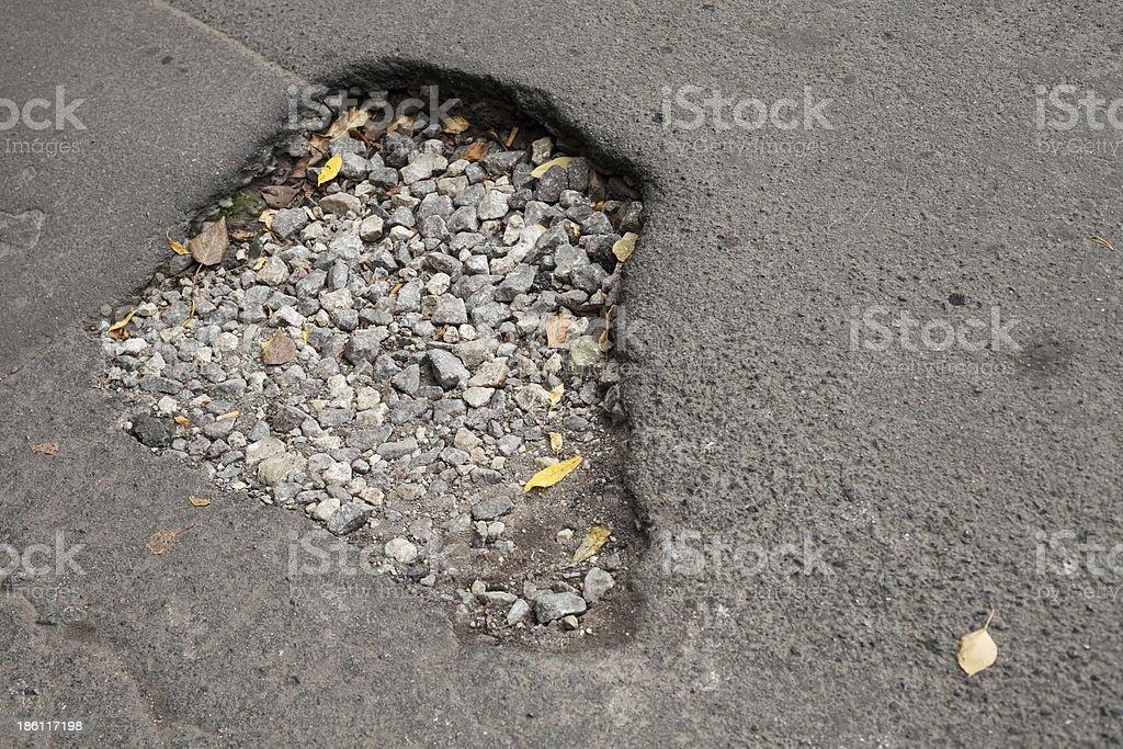 Pothole with gravel on damaged urban asphalt road royalty-free stock photo