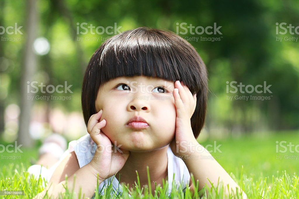 Potrait of Little Asian Girl Lying in Grass royalty-free stock photo