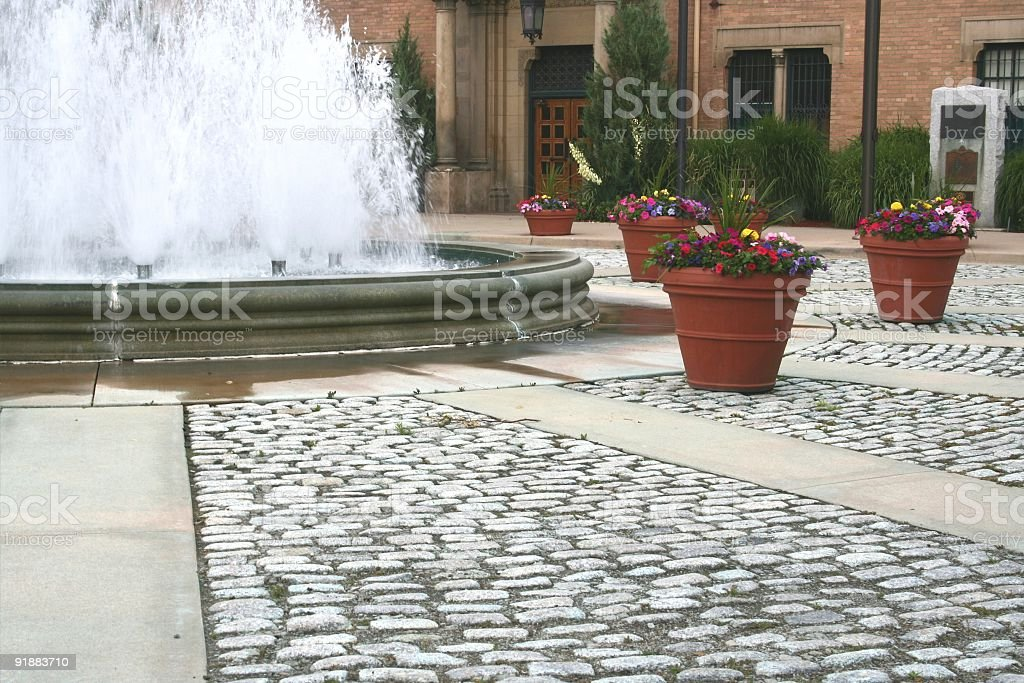Potted flowers, cobblestone, and fountain stock photo