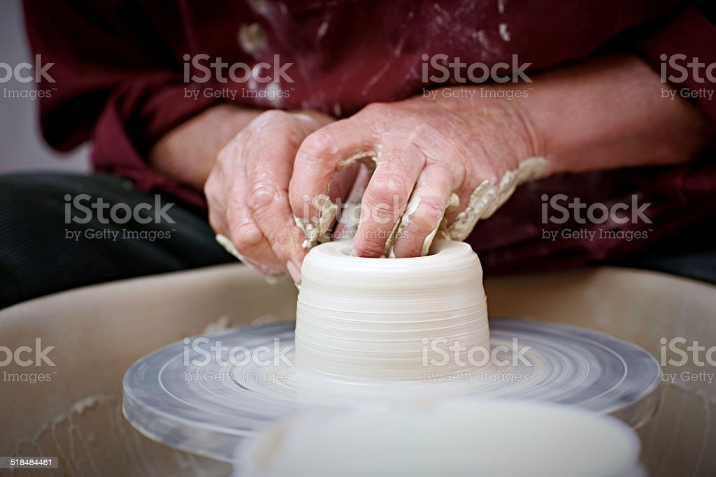 Potter at work moulding a clay pot stock photo