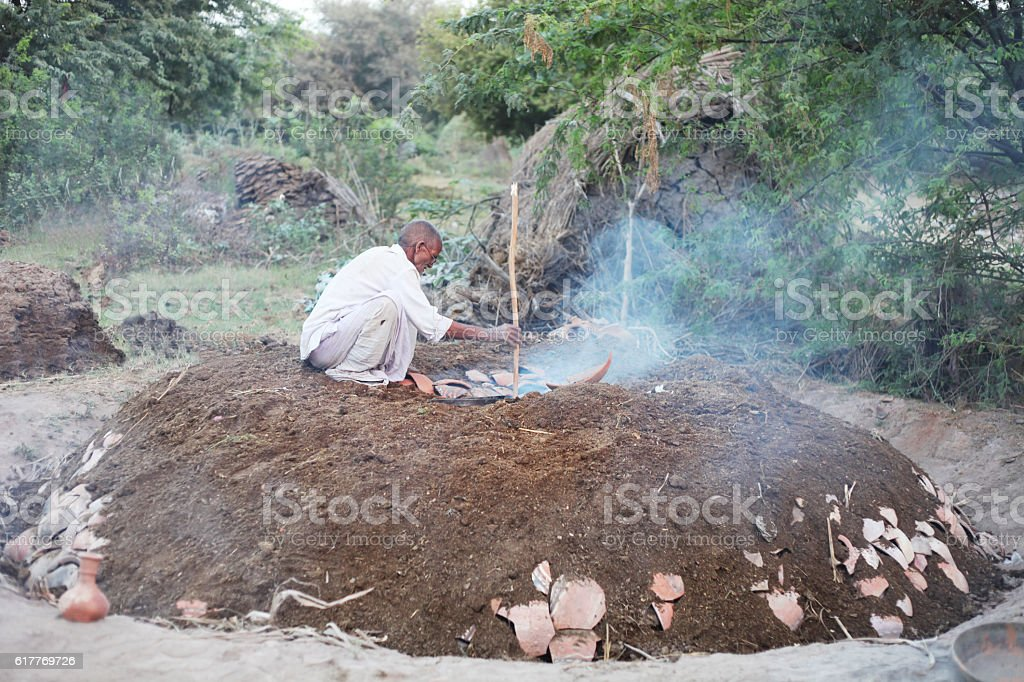 Potter baking pots in furnace using cow dung cake stock photo